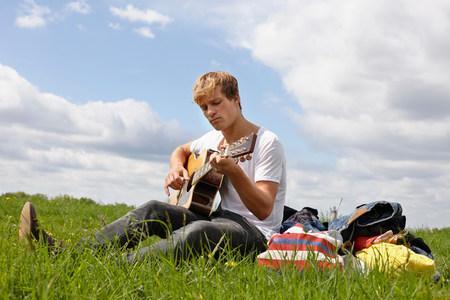 plants species: Giovane che gioca chitarra su erba