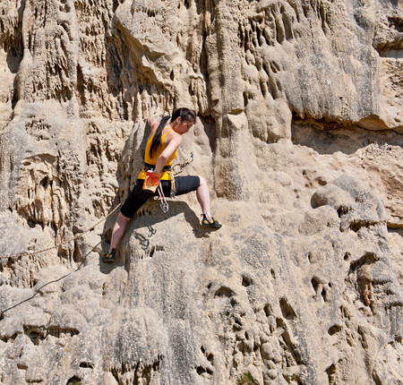 tallness: Female rock climber on rock face LANG_EVOIMAGES