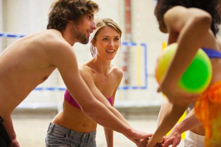Friends having team talk at indoor beach volleyball