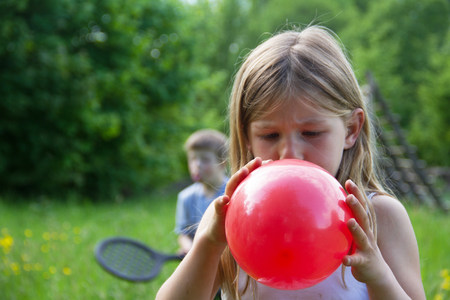 Close portrait of young girl blowing up red balloon