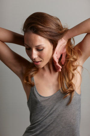 armpits: Studio portrait of young woman with hands in hair