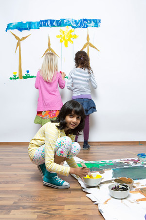 Girls painting wind turbines on wall