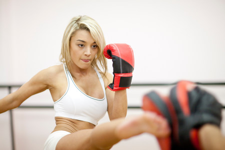 Young woman kickboxing in gym