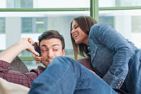 jesting: Young couple at home messing about with mobile phone