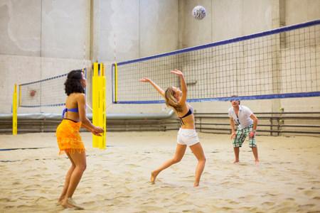 sinergia: Amigos jugando voleibol de playa cubierto