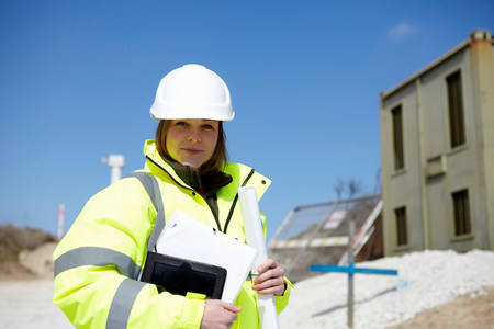 Portrait of female with blueprint and digital tablet on construction site