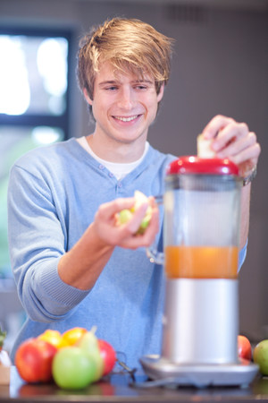 Young man preparing fruit drink