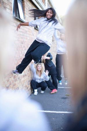 exerting: Teenage girl dancing against brick wall LANG_EVOIMAGES