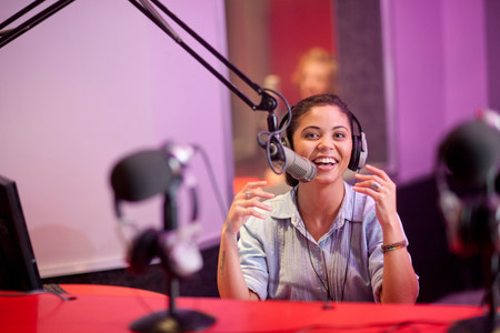 purples: Young woman broadcasting in recording studio,portrait LANG_EVOIMAGES