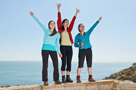 Three female friends waving from wall at coast