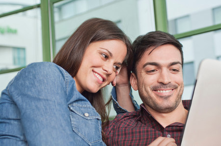 parlours: Happy young couple looking at digital tablet
