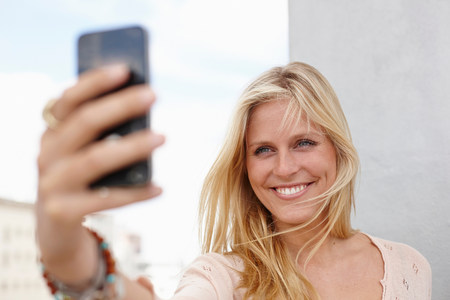 off shoulder: Young woman taking self portrait on smartphone
