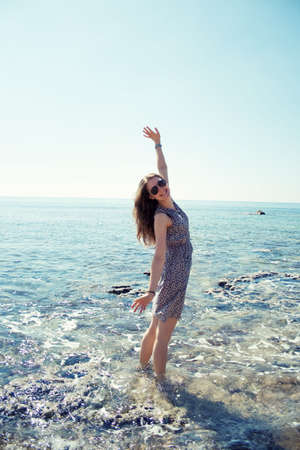 Young woman standing in sea with arms up