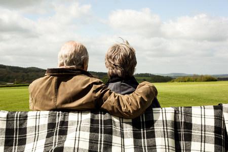 living idyll: Back view of senior couple enjoying scenery on field