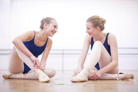 rumour: Two ballerinas chatting whist fastening ballet slippers LANG_EVOIMAGES