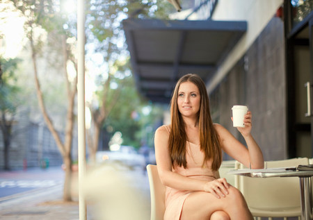 Young woman holding coffee in street cafe