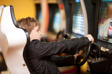 level playing field: Boy playing on driving video game