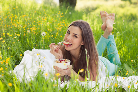 Woman in field of buttercups eating fresh fruit LANG_EVOIMAGES