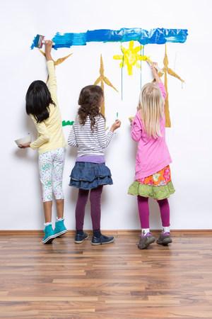 Three girls painting wind turbines on wall