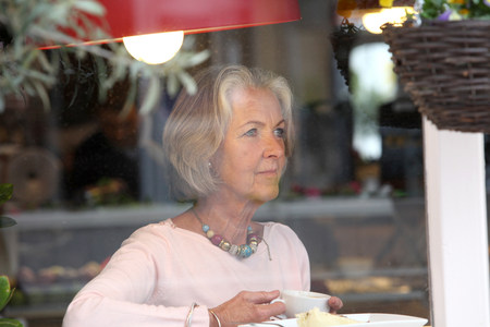 Senior woman holding coffee cup in cafe