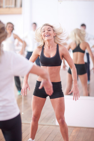 Young woman jumping in aerobic class