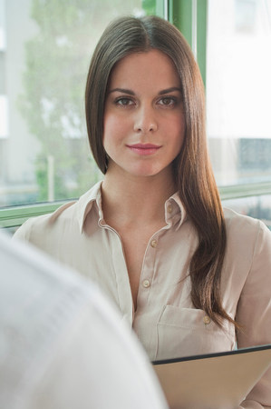 Portrait of young female in office holding digital tablet