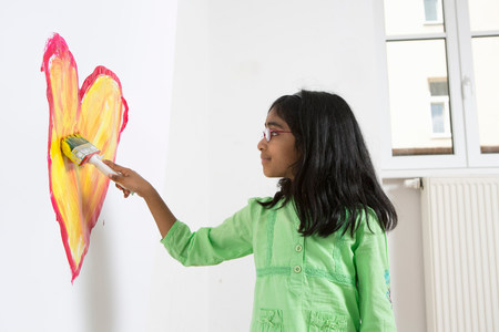 Girl painting heart shape on wall