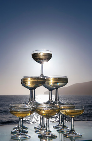 refreshed: Champagne glasses in pyramid shape with sea in background