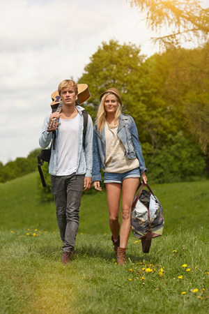 only one teenage boy: Young couple walking through field with guitar
