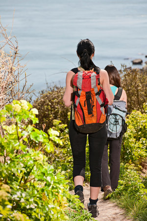 Two female friends walking down coastal path LANG_EVOIMAGES