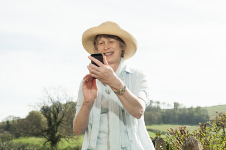 living idyll: Senior woman smiling at message on mobile phone
