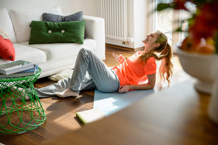 parlours: Young woman holding smartphone whilst lounging on floor