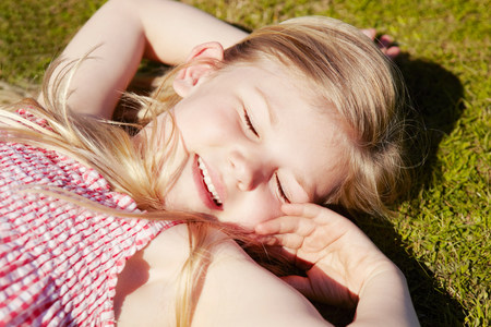 'eyes shut: Child lying down on grass