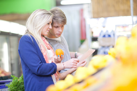 shopper: Young couple buying oranges in indoor market LANG_EVOIMAGES