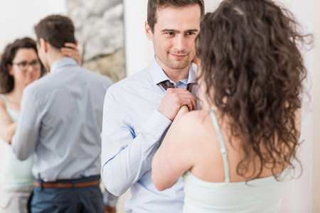 35 to 40 year olds: Mid adult woman helping man to fasten tie