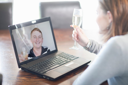 parlours: Woman toasting husband using video call LANG_EVOIMAGES