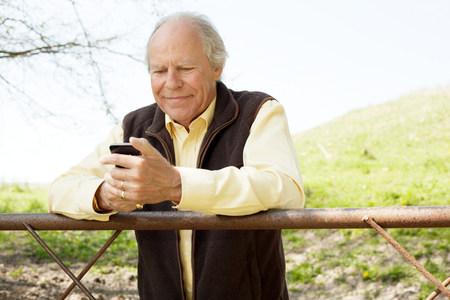 living idyll: Senior man smiling at message on mobile phone