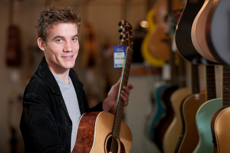 Young man looking at guitars in music store LANG_EVOIMAGES