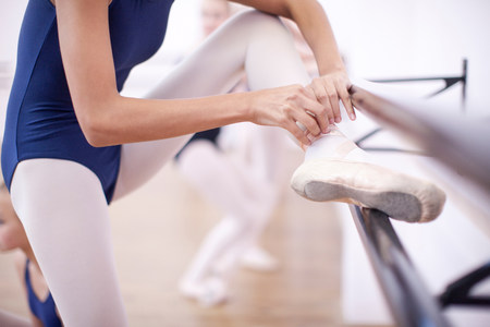 Ballerina fastening ballet slipper at the barre LANG_EVOIMAGES