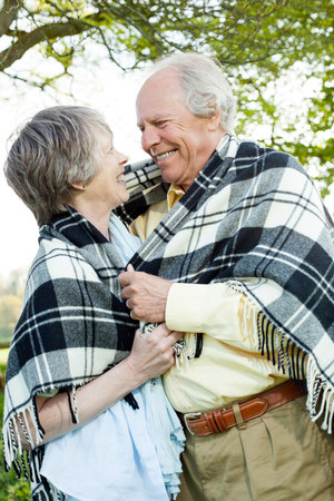 60 64 years: Senior couple wrapped in shawl together LANG_EVOIMAGES