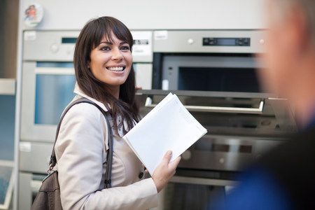 shopper: Woman looking at oven in showroom