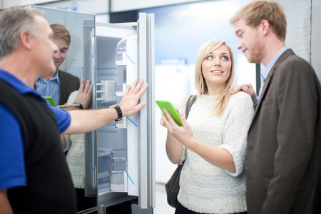home improvement store: Young couple looking at fridge in showroom LANG_EVOIMAGES