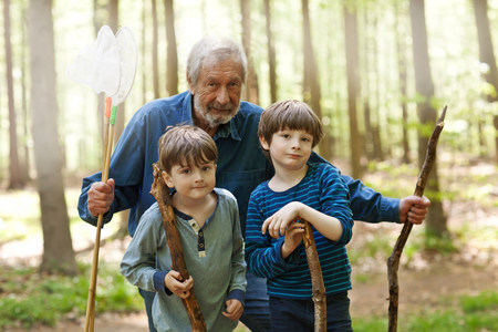 6 7 year old: Grandfather and grandsons holding sticks in forest,portrait