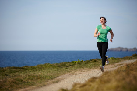 Young woman running along coastal path
