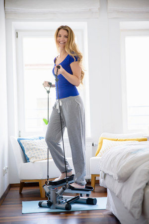 athleticism: Young woman using step machine at home