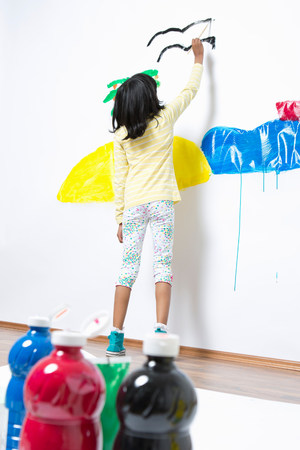 Girl painting ocean and island on wall LANG_EVOIMAGES