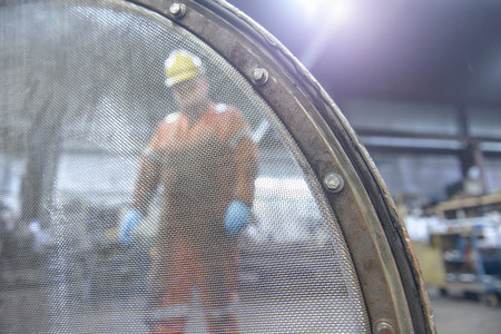low perspective: Portrait of worker behind industrial sieve in steel foundry LANG_EVOIMAGES