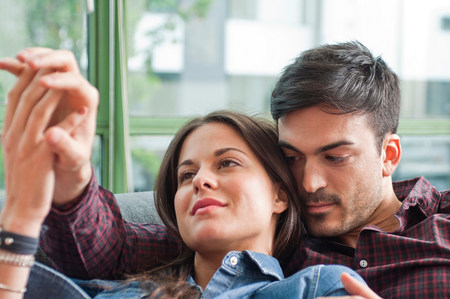 parlours: Young couple lounging on sofa holding hands