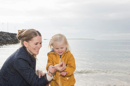 all under 18: Mother and toddler exploring at coast