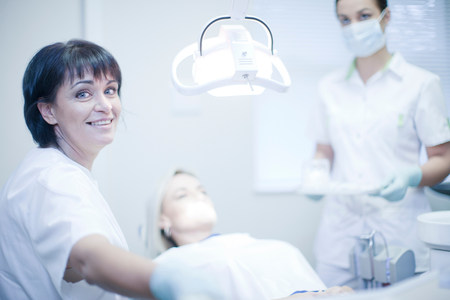 down lights: Portrait of female dentist with nurse and patient